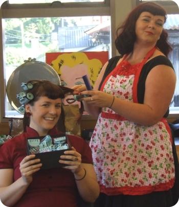 Miss Tittle Tattle of Debonaire Doos curls the hair of Miss La Belle. In the background, Marilyn Monroe approves.