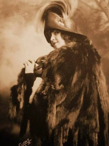 1920s arcade card featuring Fannie Ward and a sable coat ready to run away on all those feet!